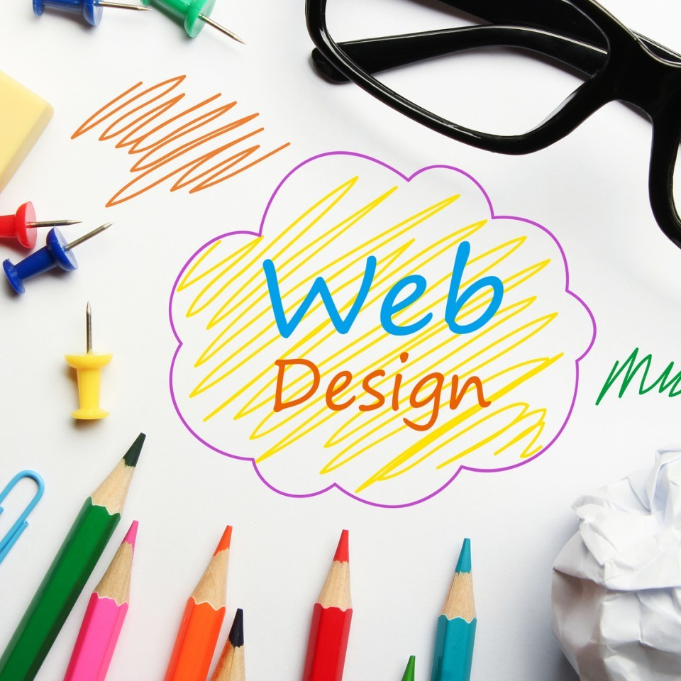 Web design concept with some office supplies around it on white background.