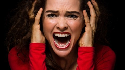 Close-up of a very angry, upset and desperate woman screaming