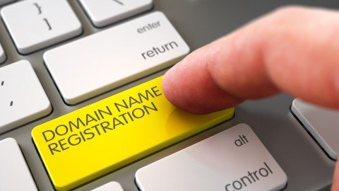 Close Up view of Male Hand Touching Yellow Domain Name Registration Computer Keypad. 3D.