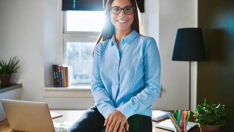 Relaxed confident young businesswoman or entrepreneur wearing glasses sitting on the edge of her desk in a home office smiling at the camera