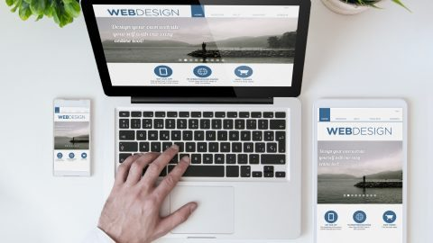 office tabletop with tablet, smartphone and laptop showing web design website. All screen graphics are made up.